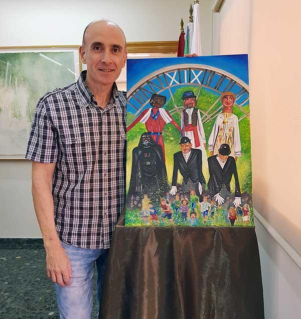 """Jesús Honrubia, autor del cartel anunciador del XIX Encuentro Nacional de Gigantes y Cabezudos """"Villa de Abarán"""", junto a su obra."""