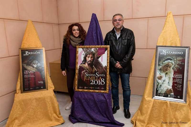 José Luis Miñano, junto a su hija, posan al lado del cartel anunciador de 2018 del que fue también autor.